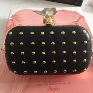 Black clutch with gold skull with rhinestones.